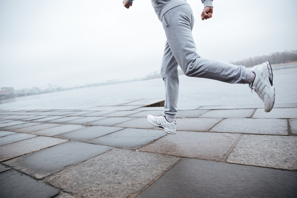 Cropped image of man in gray sportswear running near the water. Left view