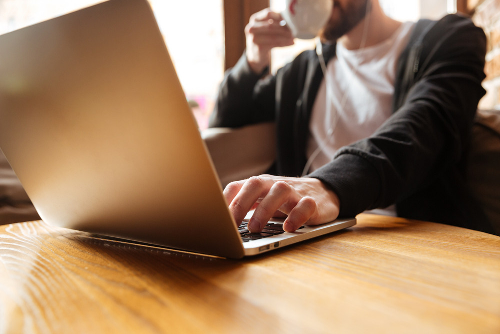 Cropped image of man sitting by the table with laptop in cafe near the window and drinking coffee