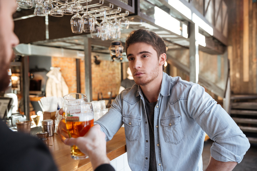 Cropped image of man with his friend drinking beer and sitting on bar