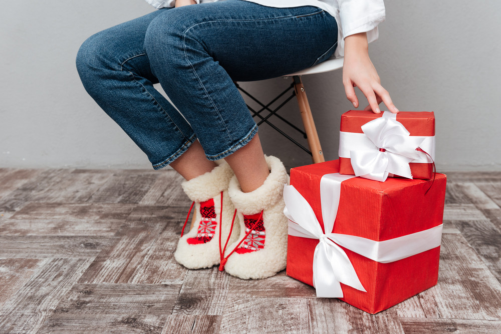 Cropped image of pregnant woman with gifts. sitting on chair