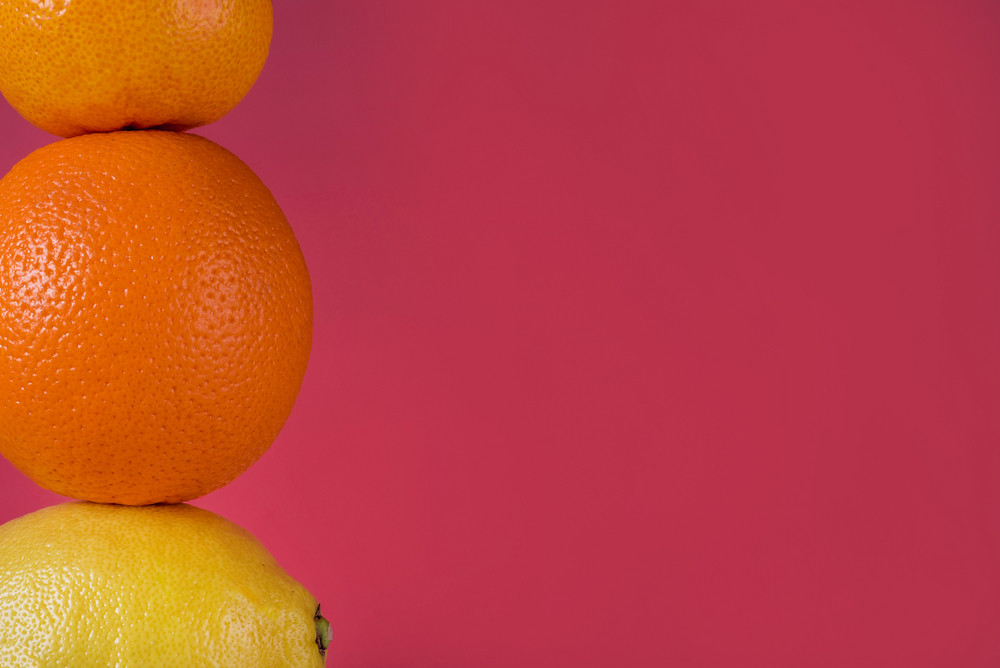 Cropped image of ripe fresh citrus fruits, tangerine fruit, orange isolated on pink background