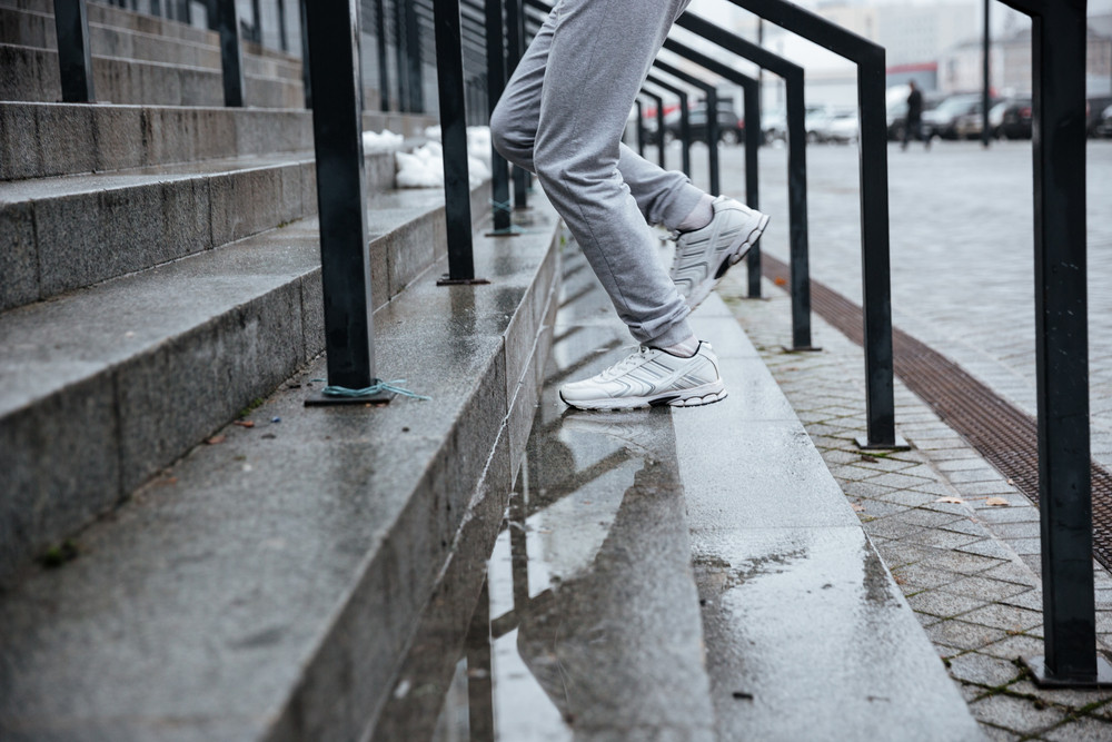 Cropped image of runner in gray sportswear running on stairs