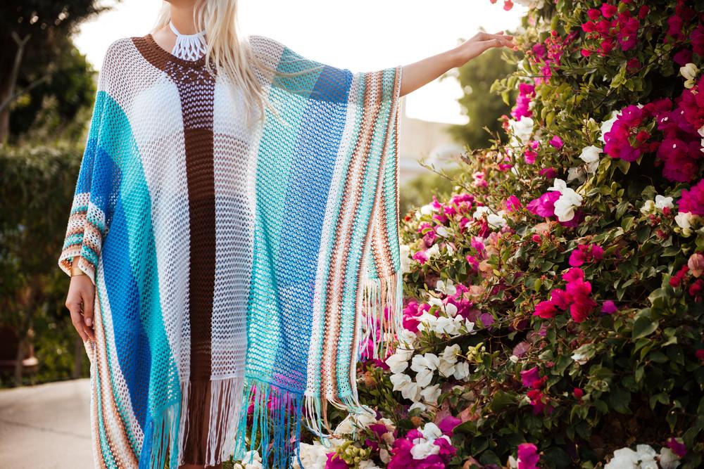 Cropped image of Woman in beachwear which posing near the flower bush