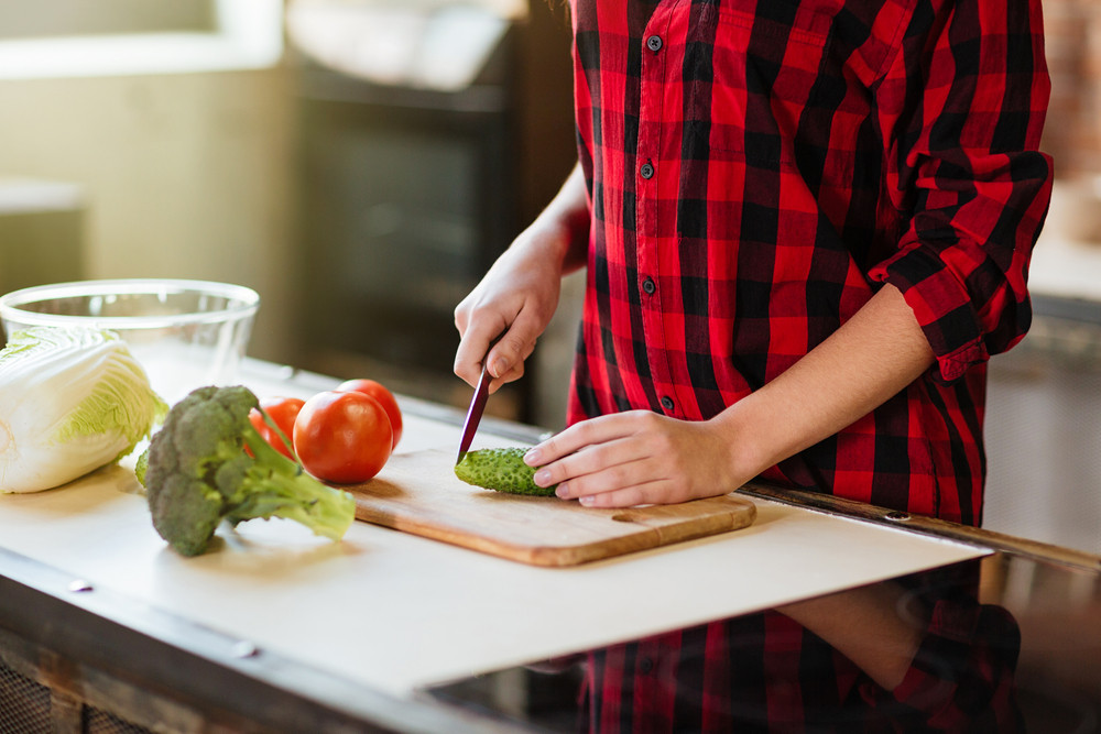 Cropped image of woman in red shirt cooking in kitchen. Side view