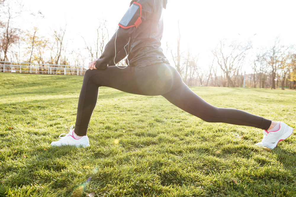 Cropped image of woman runner in warm clothes in autumn park early morning make sport exercise. Lens flare.