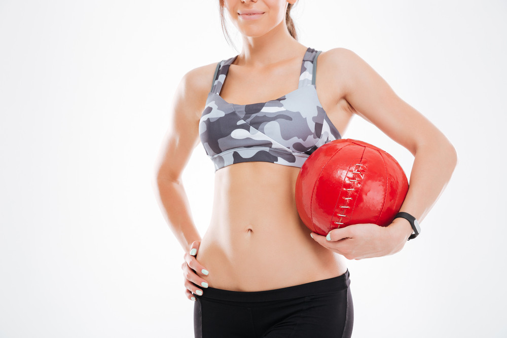 Cropped image of woman with ball in studio. isolated white background