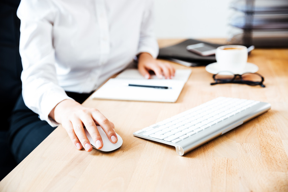 Cropped image of women's hands using keyboard and mouse at the office