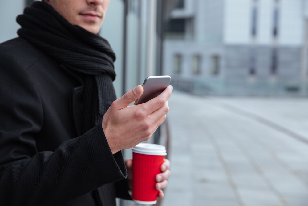 Cropped image of young business man in warm clothes with coffee and phone outdoors
