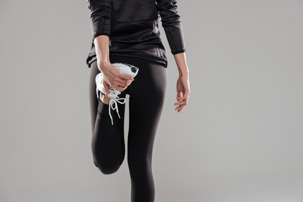 Cropped image of young fitness lady standing over grey background.