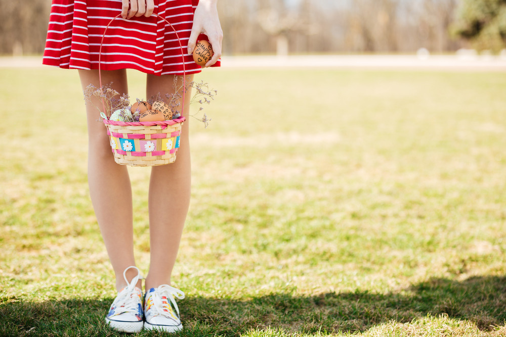 Cropped image of young girls legs and arms holding basket with painted easter eggs outdoors