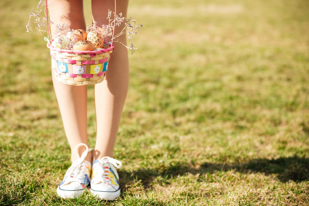 Cropped image of young girls legs and basket with painted easter eggs outdoors