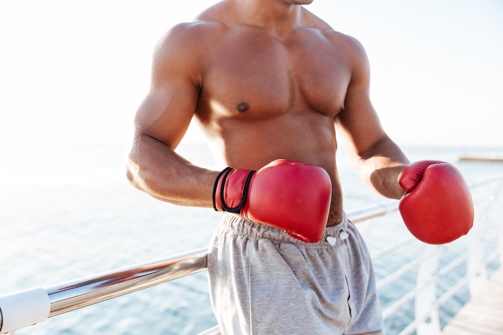 Cropped image of young healthy afro american sportsman in red gloves doing boxing exercises at the pier outdoors