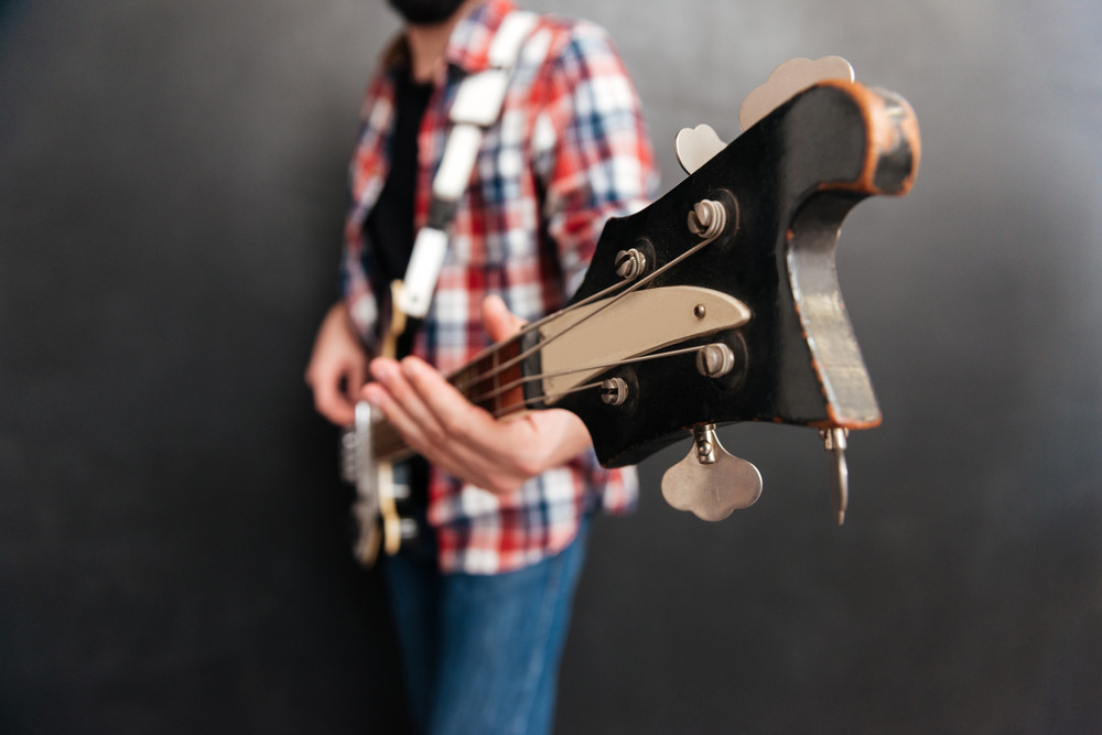 Cropped image of young man dressed in shirt in a cage standing over chalkboard while playing on the guitar. Music concept.