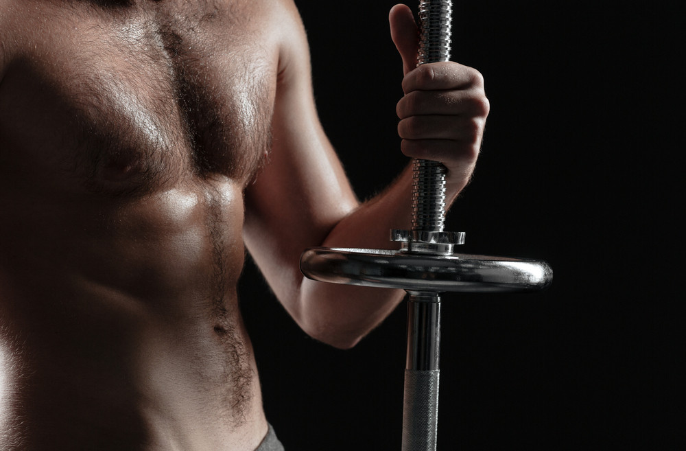 Cropped naked athletic man with barbell. isolated dark background