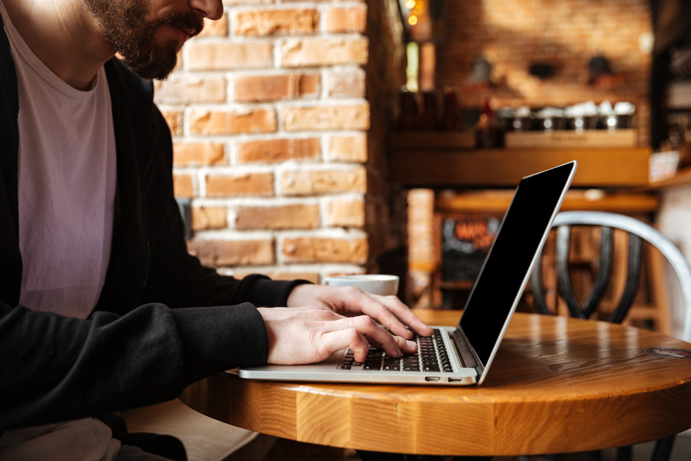 Cropped omage of Bearded man sitting by the table and using laptop in cafe