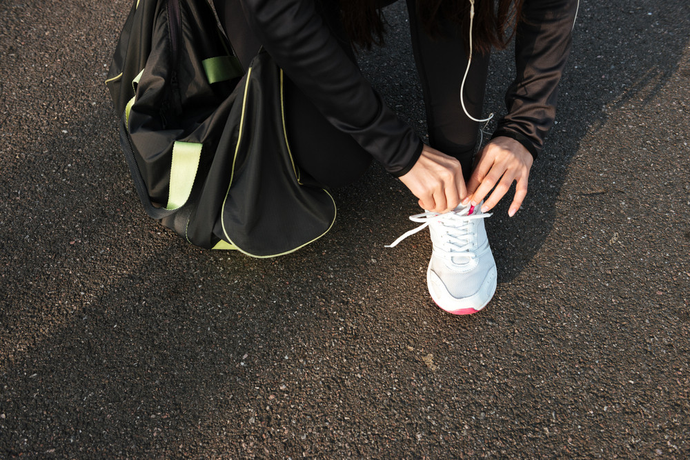 Cropped photo of woman runner dressed in warm clothes tying laces before training.