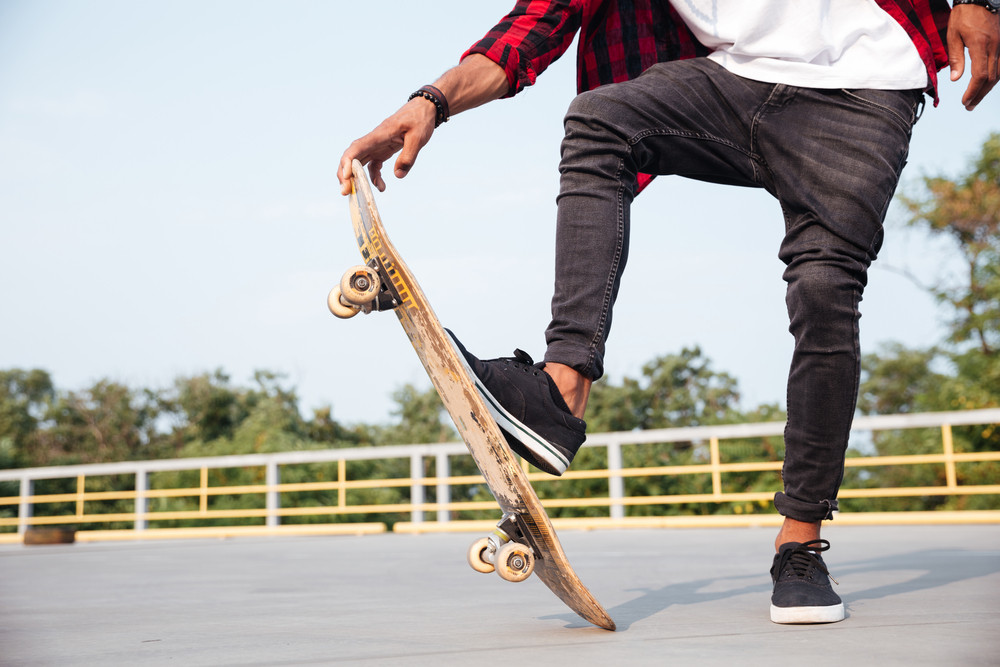 Cropped photo of young dark skinned man skateboarding. Against the nature background.