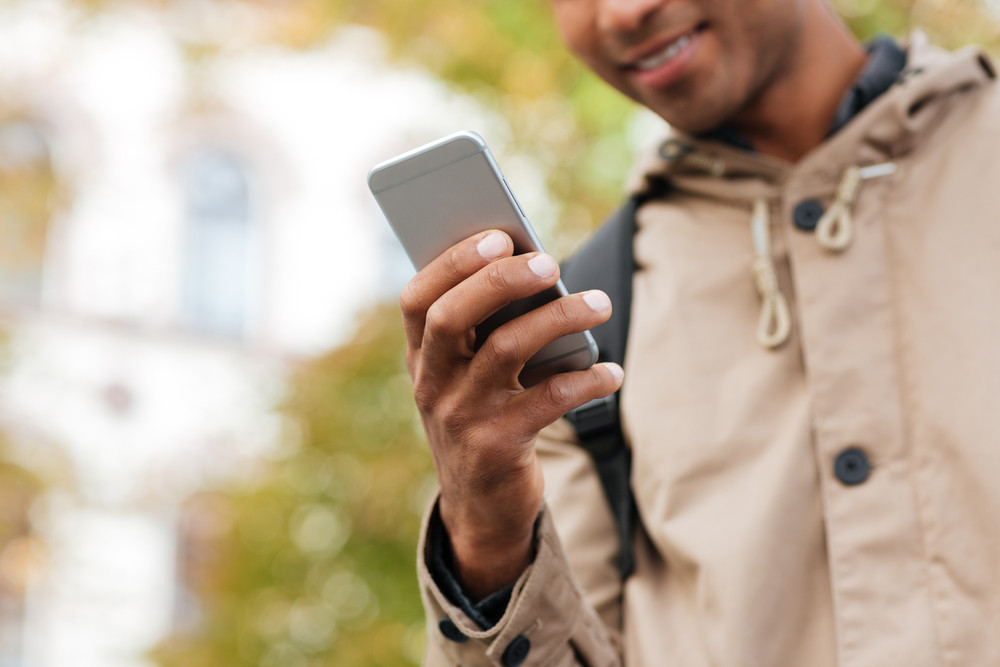 Cropped photo of young dark skinned man using his cellphone on the street.
