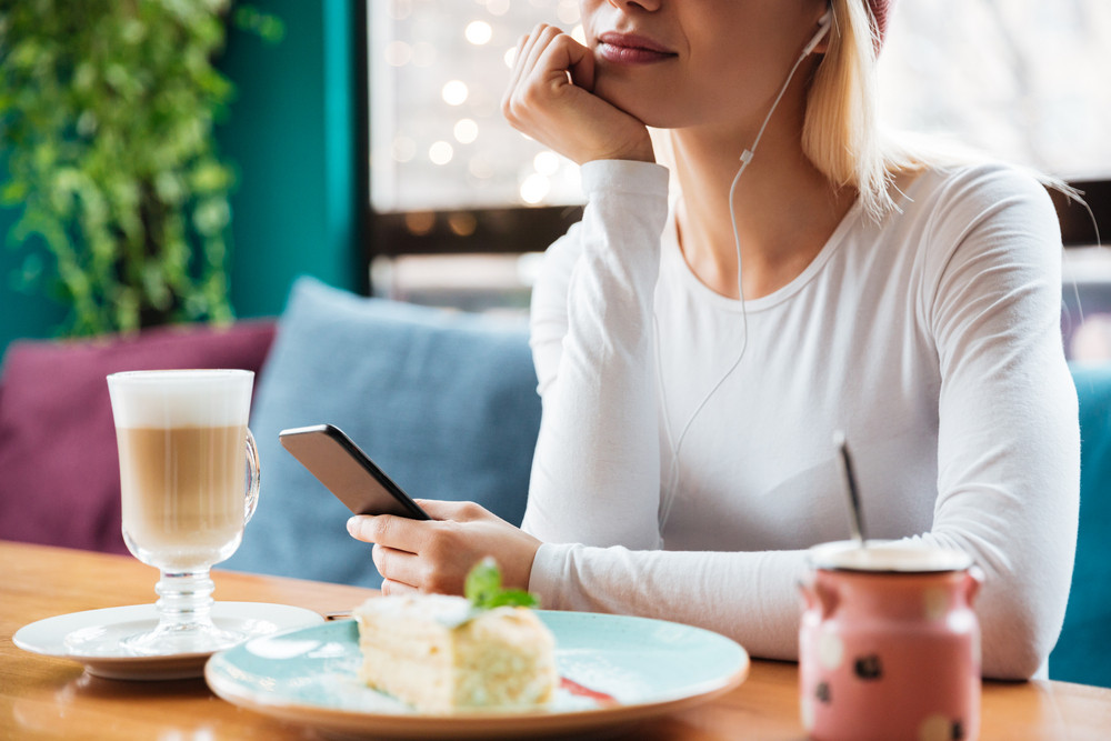 Cropped photo of young lady listening music with earphones and holding phone sitting in cafe.