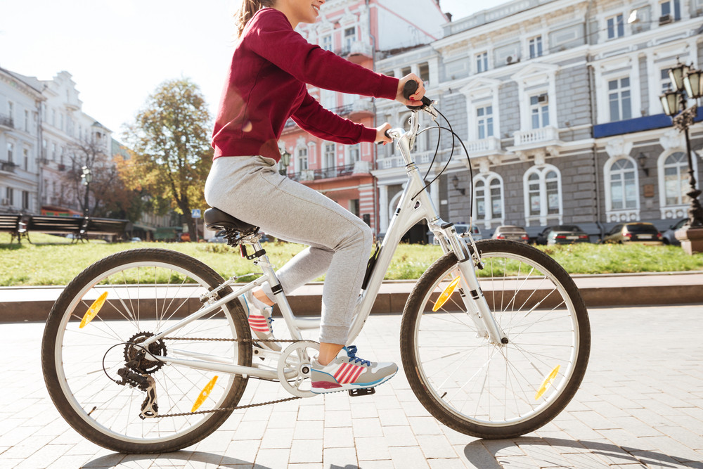 Cropped photo of young woman dressed in sweater walking with her bicycle in the city.