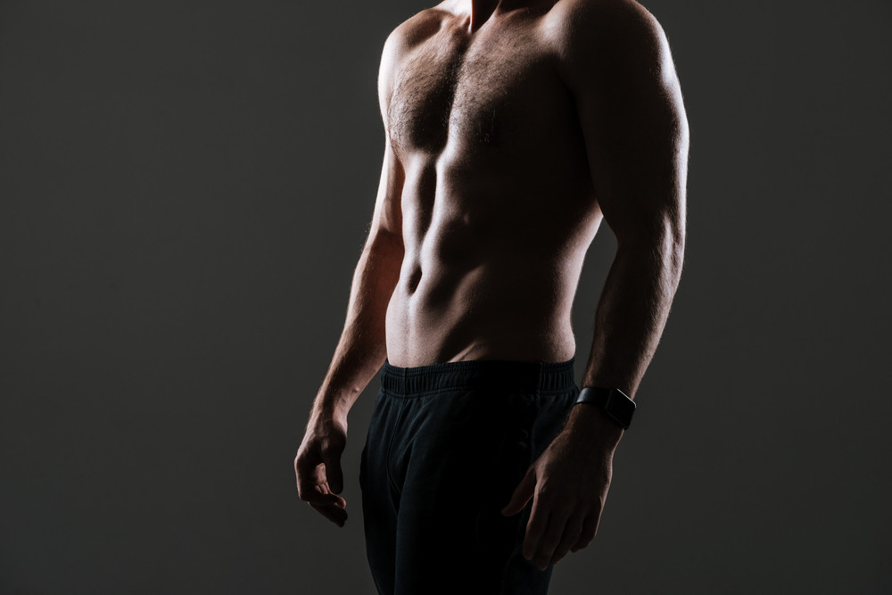 Cropped picture of attractive sportsman standing in gym over grey background.