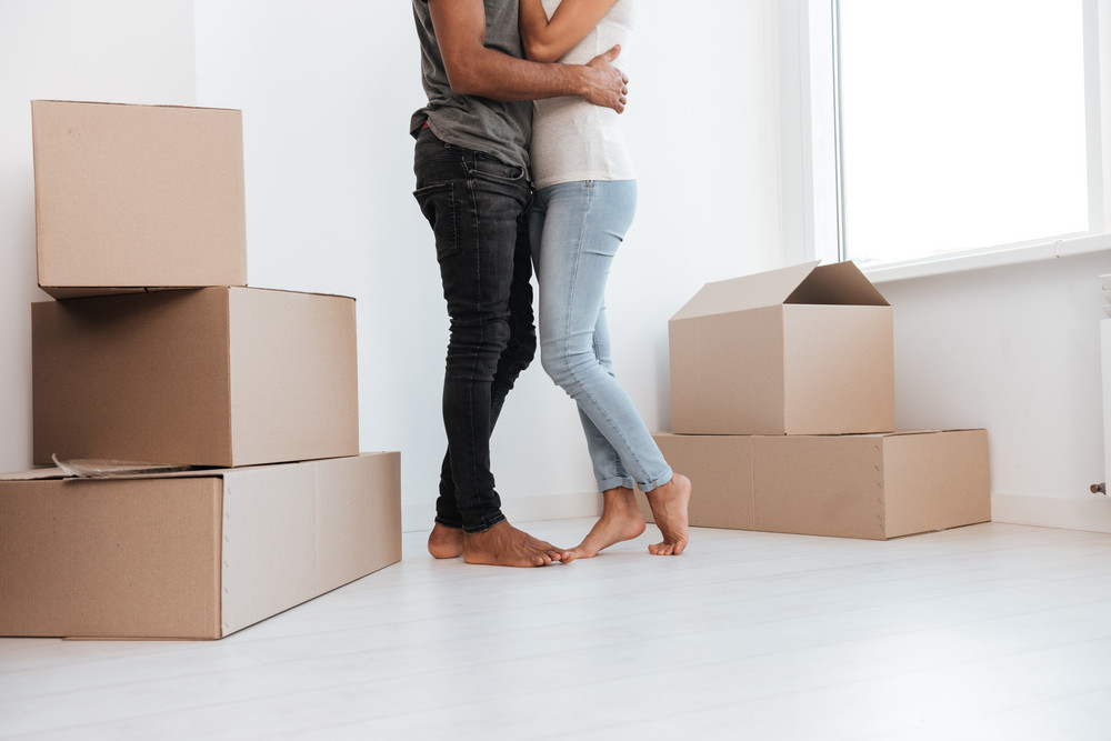 Cropped picture of happy couple hugging while standing near unpacked boxes.