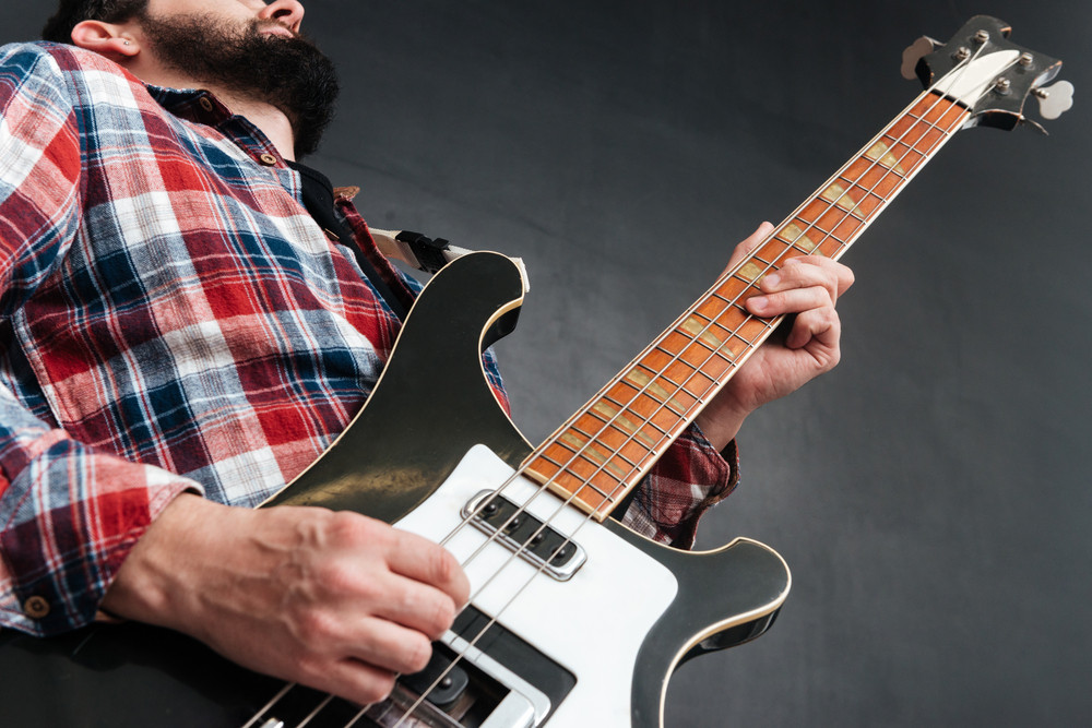 Cropped picture of man dressed in shirt in a cage standing over chalkboard while playing on the guitar. Music concept.