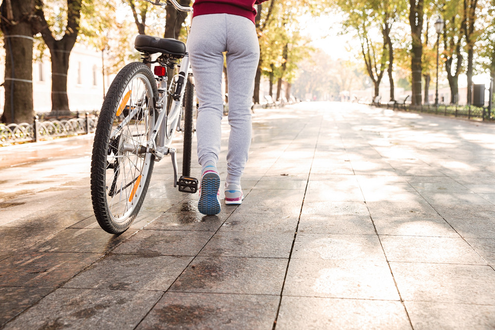 Cropped picture of young caucasian woman walking with her bicycle in the street