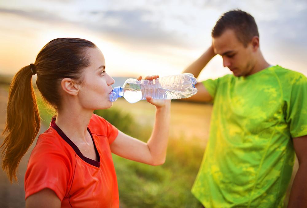 Cross-country trail running couple having water break at sunset