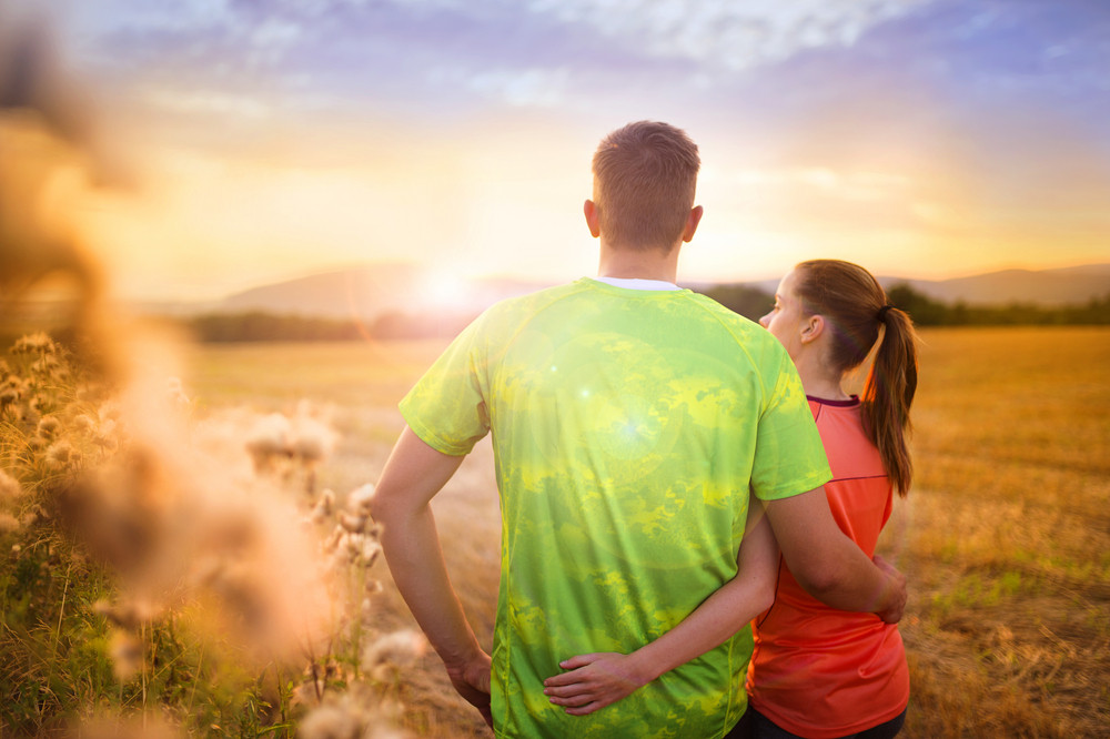 Cross-country trail running couple relaxing and watching the sunset