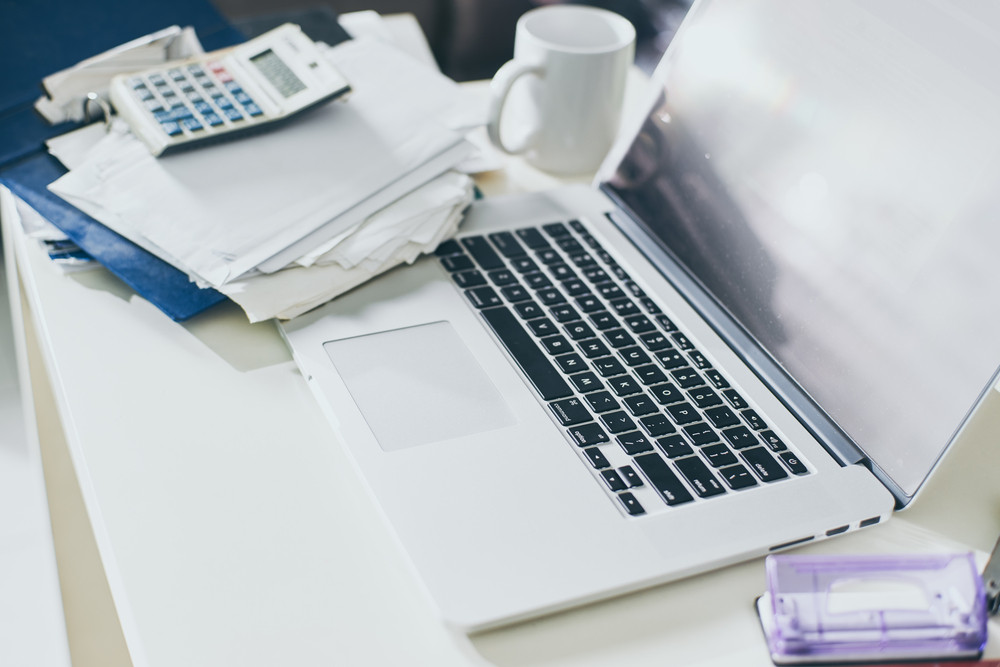 Cup of coffee, documents and laptop on the table of business person