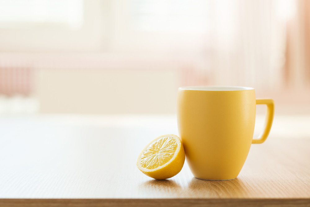Cup of tea and lemon closeup with sunny house interior in background