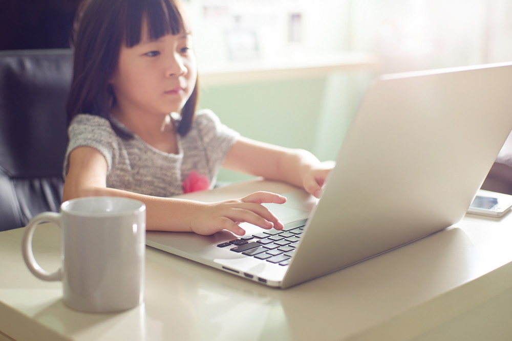 Cute asian little girl using laptop at home . Seleted focus.