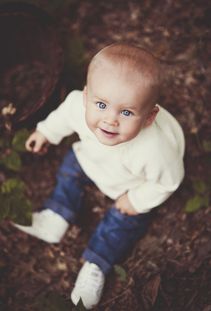Cute baby boy sitting in the forest