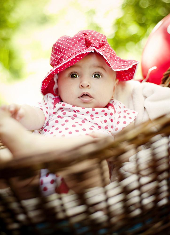 Cute baby girl lying down in basket in summer nature