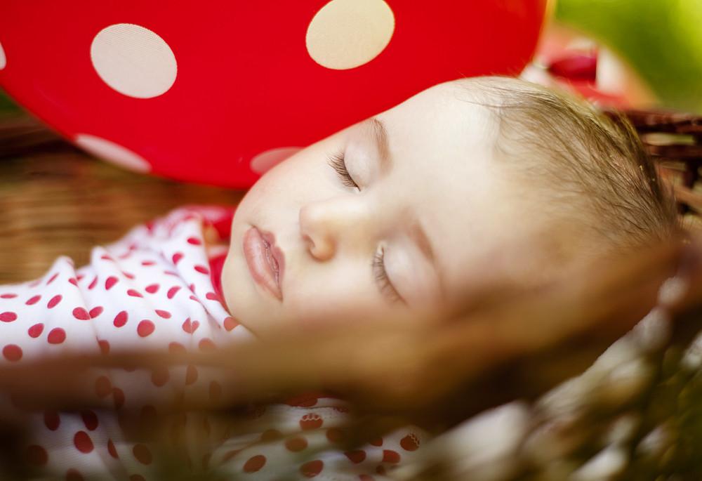 Cute baby girl sleeping in basket in summer nature