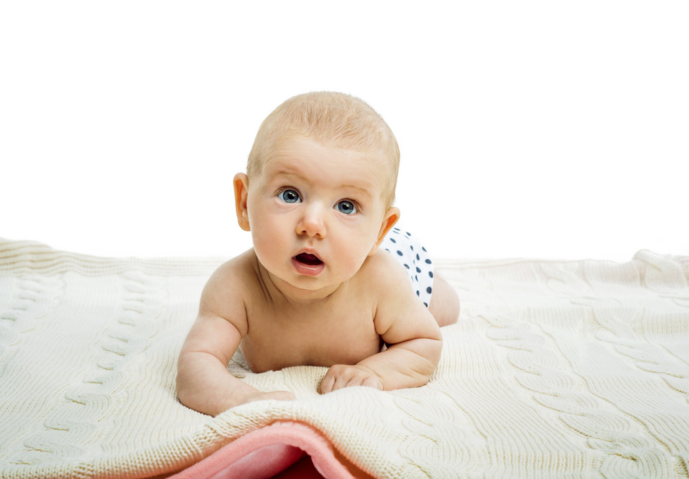 Cute baby lying on a floor isolated on white background