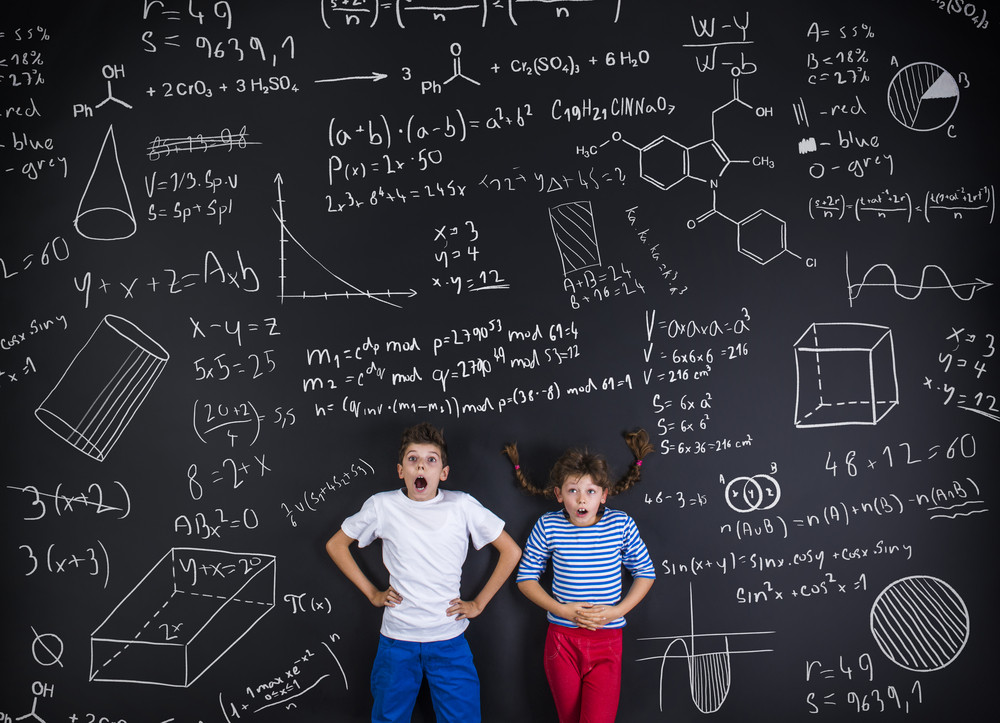Cute boy and girl learning playfully in frot of a big blackboard