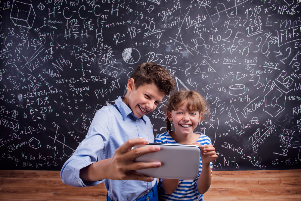 Cute boy and girl with smart phone, taking selfie, at school in front of a big blackboard. Studio shot on black background.