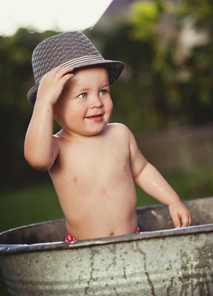 Cute funny little boy in hat bathing in galvanized tub outdoor in green garden