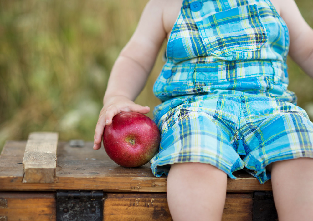Cute kid holding a red apple in green park