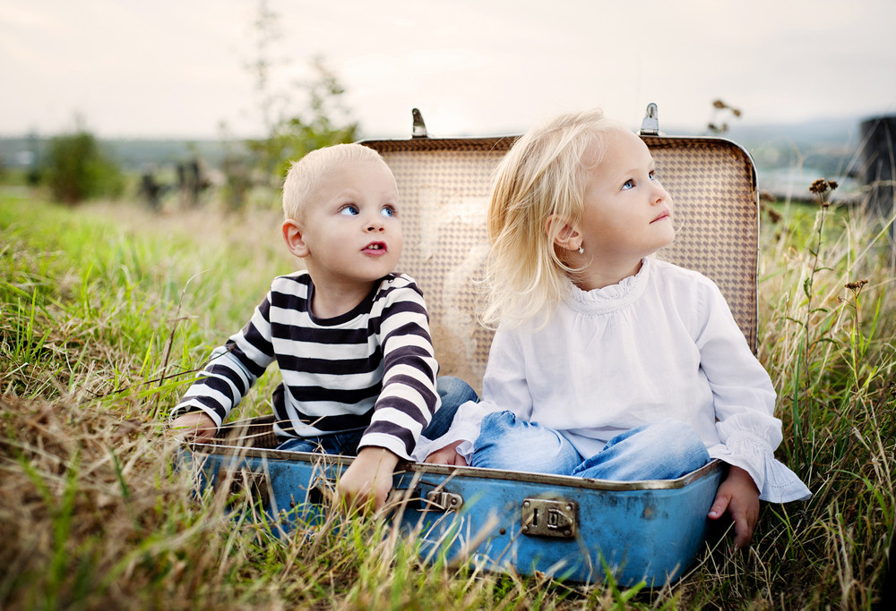 Cute kids are having fun in the old suitcase