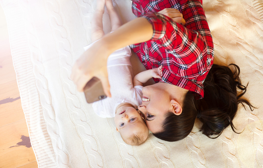 Cute little baby girl and her mother taking selfie on a blanket in a living room.