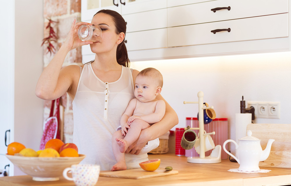 Cute little baby in the arms of her mother in their kitchen.