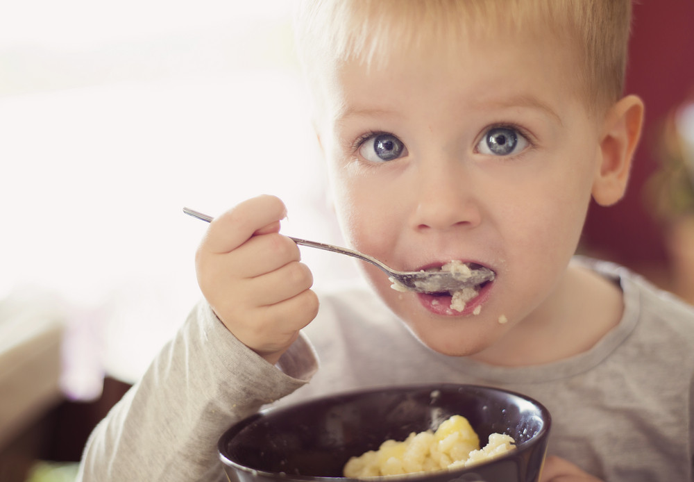 Cute little blonde boy eating pasta from black bowl