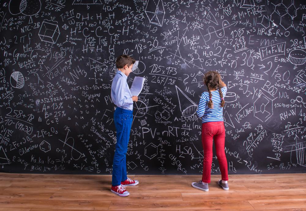 Cute little boy and girl in front of a big blackboard. Studio shot on black background.