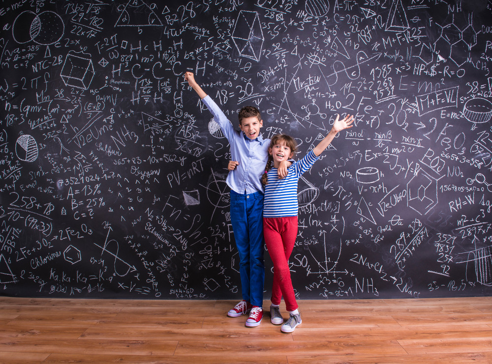 Cute little boy and girl in front of a big blackboard. Studio shot on black background.