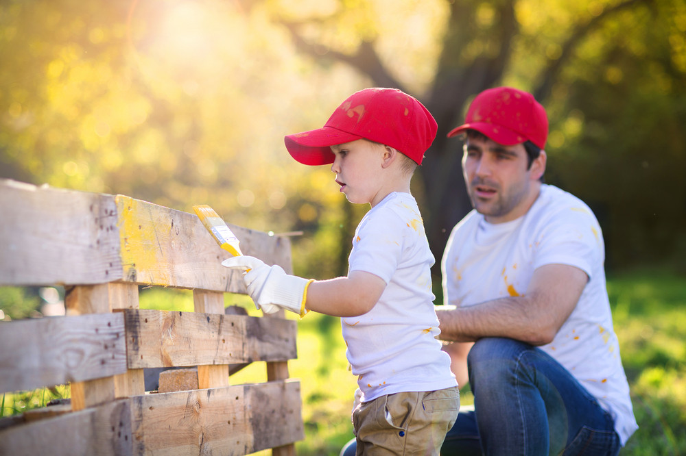 Cute little boy and his father in red caps painting wooden fence together  on sunny day ed6b20f6ca5a