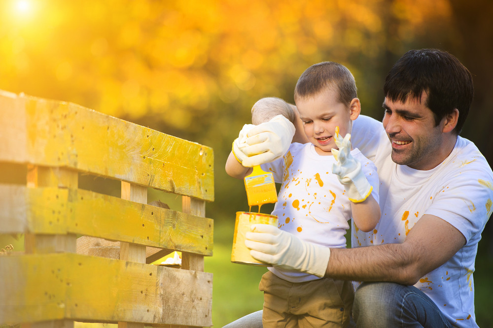 Cute little boy and his father painting wooden fence together on sunny day in nature