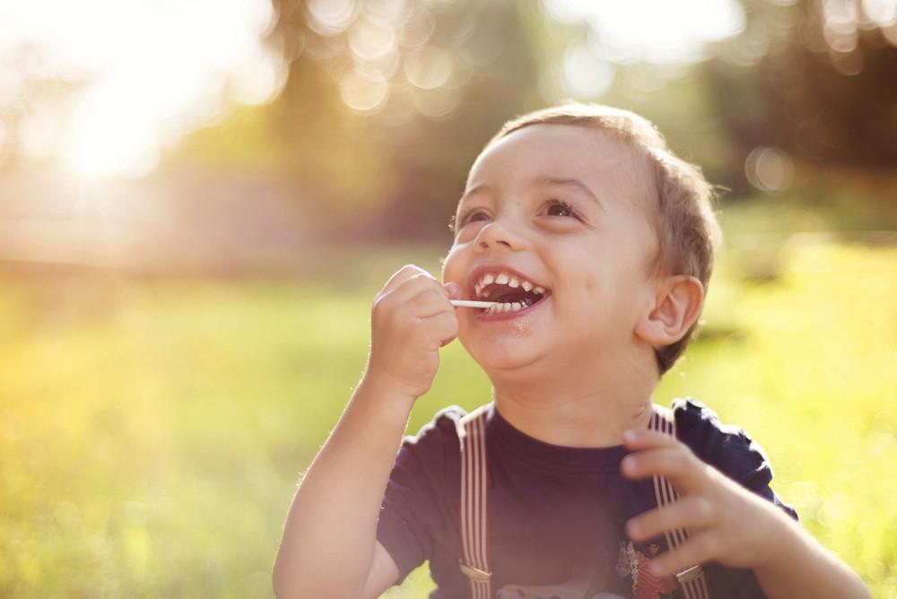 Cute little boy having fun outside in summer nature